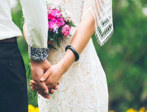 brautpaar haelt sich an der hand braut hat brautstrauss in der hand